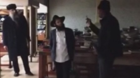The suspected assailant, right, exchanging words with a Jewish man inside the Chabad headquarters in New York on December 9, 2014. (Screen capture: YouTube)