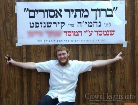 Nechemia Kirshenzaft posing in front of a sign celebrating his release.